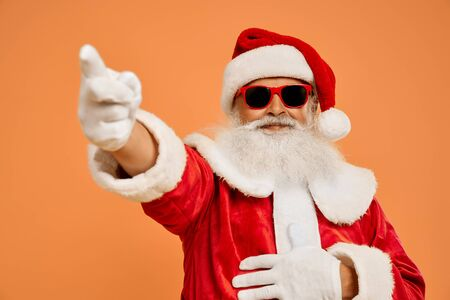 Senior bearded man in red Santa costume and trendy sunglasses over isolated background looking at camera and pointing on by finger. Front gesture and positive emotion.