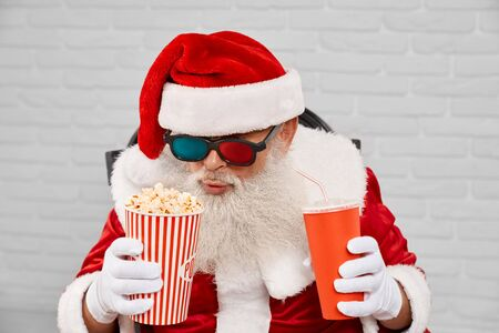 Senior man wearing traditional santa claus costume and 3d glasses, sitting in cozy armchair with popcorn and cola in white studio. Funny christmas character enjoying free time.