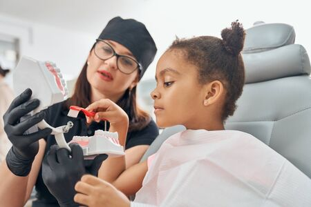 Female dentist in medical uniform and black hat, glasses and rubber gloves holding teeth model. Doctor teaching little patient how to brush teeth. African girl sitting and holding toothbrush. Banque d'images