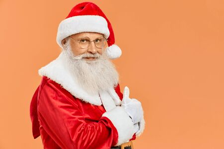 Real senior Santa Claus in traditional costume carrying on red bag and showing thumb up in white gloves. Happy Christmas Santa with gifts over orange background