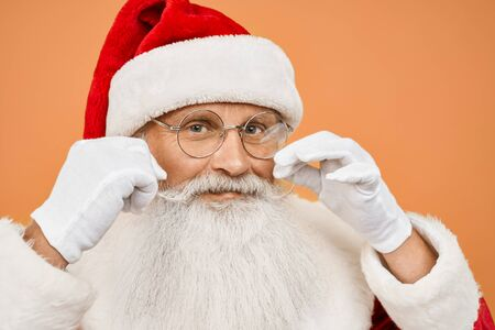 Close up of senior Santa Claus in red traditional costume, eyeglasses and white gloves twirling mustache and looking at camera over orange studio background