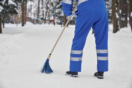 Hombre limpiando nieve con escoba. Trabajador vistiendo uniforme azul con banda de seguridad sosteniendo una escoba de plástico. Janior con herramienta para remoción manual de nieve. Concepto de servicio de la ciudad. Foto de archivo