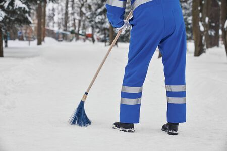 Mann, der Schnee mit Besen säubert. Arbeiter in blauer Uniform mit Sicherheitsband mit Plastikbesen. Janior mit Werkzeug zur manuellen Schneeräumung. Konzept des Stadtdienstes. Standard-Bild
