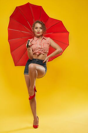 Full length portrait of adorable cheerful young lady with blonde curly hair dressed in summer clothes and red high heels standing over yellow background and keeping opened umbrella in form of heart. Reklamní fotografie