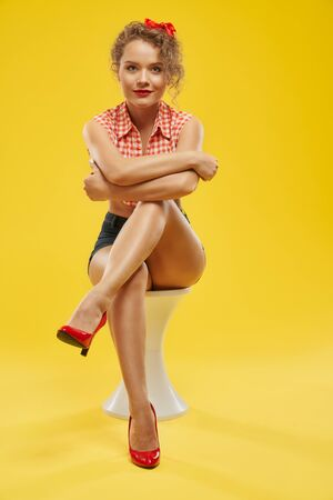 Pretty blonde glamour girl with curly hair and red bow on it wearing jeans shorts and checkered shirt, sitting on white chair over yellow background in studio. Lifestyle, fashion and people concept