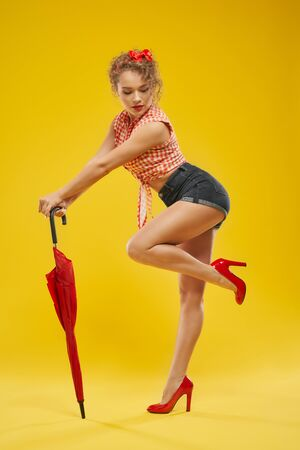 Side view of young girl with red bow in curly blond hair wearing jeans shorts,checkered shirt,high heels and leaning to closed umbrella.Pretty lady showing her sportive body and slender legs in studio