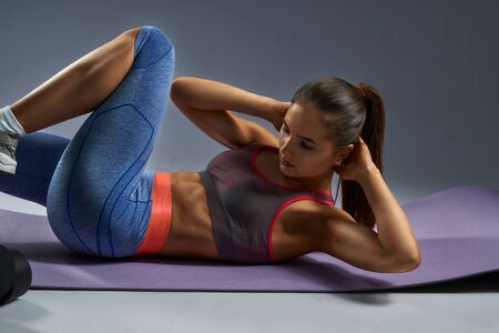 Young brunette fitness woman doing criss cross exercise for abs lying on violet yoga mat and keeping her hands behind head.Concept of healthy active lifestyle routine