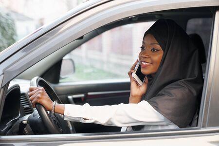 Vista dalla finestra aperta della giovane donna musulmana che parla al telefono mentre guida l'auto. Bella signora religiosa seduta nel salone nero, che tiene la ruota e ride. Concetto di veicolo e auto.