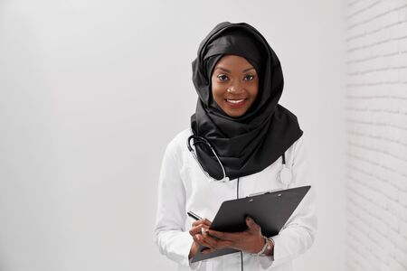 Front view of muslim woman in black hijab working in hospital. Female doctor keeping stethoscope and folder, looking at camera and posing on white isolated background. Concept of religion and care. Stock fotó