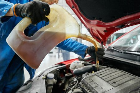 Close up of repairmans hands in black gloves keeping canister, replacing and pouring fresh oil into engine of red car. Auto maintenance,change and refuel yellow liquids