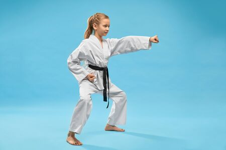 Karate girl standing in stance and punching with hand in studio. Positive, confident child in kimono with black belt practicing karate and jujitsu on blue isolated background.