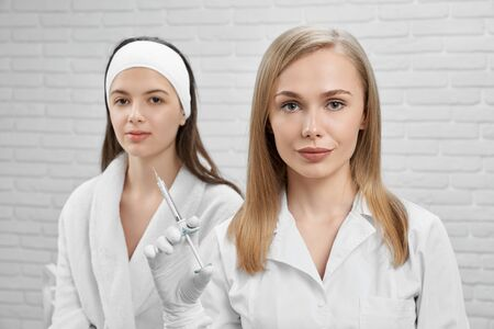 Beautiful blonde cosmetologist and pretty young woman client in cosmetic cabinet. Beautician in white coat and rubber gloves holding syringe. Client in white bathrobe. Two woman looking at camera.