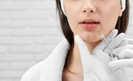 Young brunette receiving procedure of lips correction in medical centre. Hands of cosmetologist in white rubber medical gloves supporting female chin, holding syringe, making injection.