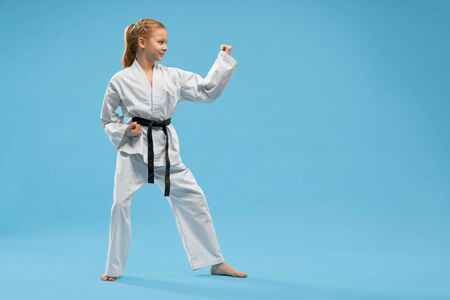 Positive, confident girl in fighting stance of karate. Happy child in white kimono with black belt practicing martial arts. Attractive kid with barefood posing in studio on blue background.