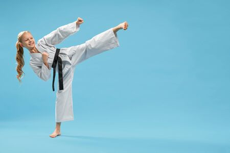 Attractive karate girl practicing kick foot forward. Cheerful, pretty child in white kimono with black belt , barefood posing in studio on blue background. Positive kid in pose of karate.