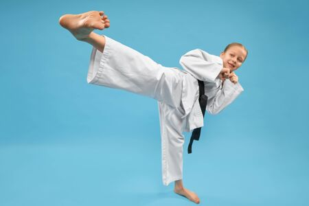 Pretty girl in white kimono and black belt practicing karate. Young positive child performing kick foot forward. Cute girl in pose of karate in studio on blue background close up.