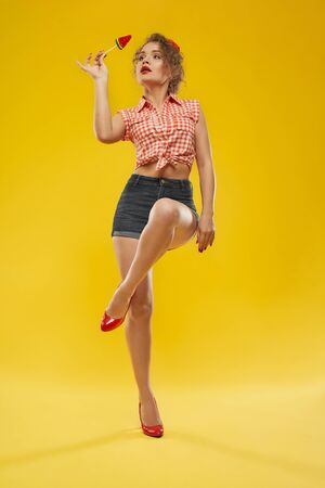 Full length portrait of stylish beautiful girl with wavy blonde hair in summer outfit standing over yellow background in red high heels with one leg lifted and crossing other leg,keeping candy in hand