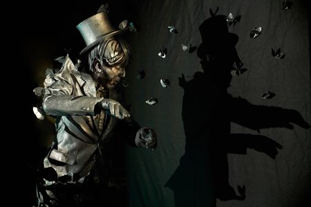 Side view of professional mime showing expressive emotions, dressed like bronze statue with lot of artificial butterflies around which seem to pull him for suit and hat.Concept of pantomime act