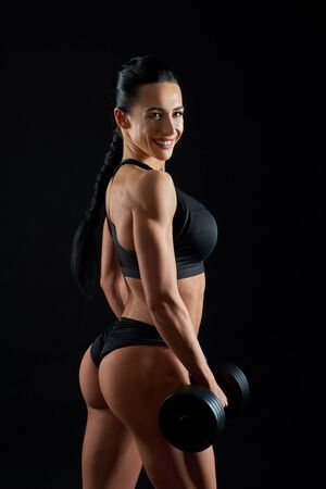 Sportive, brunette standing with dumbbell, looking at camera. Beautiful, attractive girl with muscular body and sexy buttocks in black sportswear posing on black background. Banco de Imagens