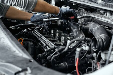 Close up of mans hands in dirty rubber gloves using wrench under opned bonnet to remove a spark plugs from engine in auto repair garage. Experienced male mechanic checking auto before exploitation