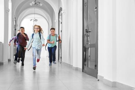 View from distance of one girl running first and other boys after, playing on school corridor together. Pupils having fun at school among lessons on break. Friendship of classmates.