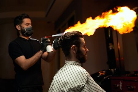 Portrait of stylish male bearded client sitting in chair and waiting while proficient hairdresser is making all preparation for haircut with fire. Concept of extreme masculinity service in barbershop