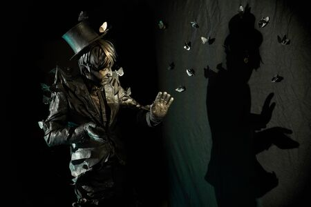 Portrait of skillful mime artist whose appearance looks like bronze statue,gesturing and showing some figure by his shadow on the black wall.Male pantomimist during working process in silent comedy