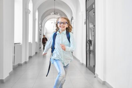 Happy blonde school girl laughing and running on lesson, so like studying. Clever girl in eyeglasses hurry up to class room. Pupil with backpack running first and happy smiling.