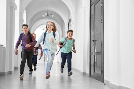 Positivity and happy pupils quickly running forward and smiling at camera. One blonde girl and three boys playing who fastest going to lesson in class room. Games in school. Stock Photo