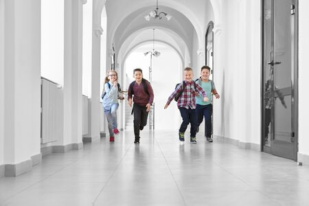 View from distance of three boys and one blonde girl playing together and running on long white school corridor. Pupils going home after hard day and lessons, feeling happy. Banco de Imagens
