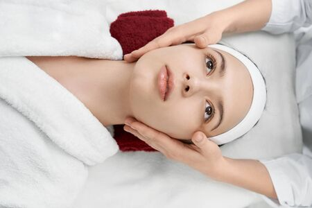 Pretty, beautiful young woman with health, well groomed face lying on massage table, looking up. Female hands of masseuse near face of client. Massage for health and beauty. Banco de Imagens