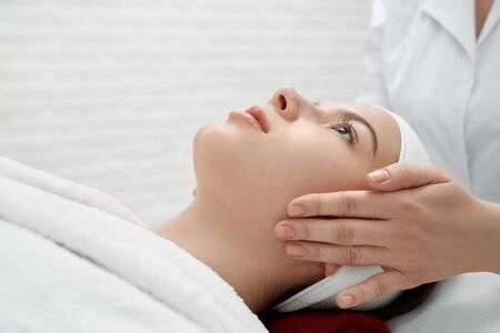 Beautiful, young woman with perfect skin and well groomed face lying on massage table, looking up. Masseuse making procedure of face massage for healthy skin and beauty. Banco de Imagens