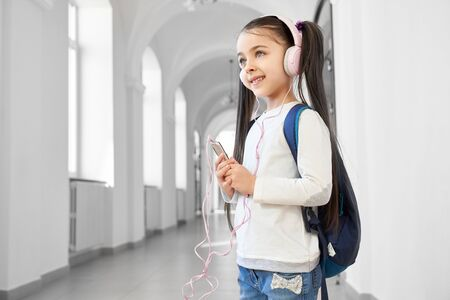 Positive and clever school girl standing in corridor of school and listening music. Little brunette girl using smartphone when resting of studying and looking away. Concept of gadgets in school. Banco de Imagens