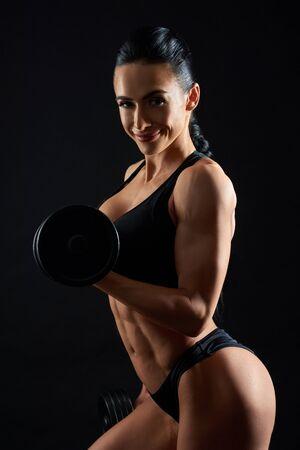 Sexy, athletische junge Frau mit dem muskulösen Körper, der mit Hantel auf schwarzem Hintergrund aufwirft. Attraktive, fröhliche Brünette, die in schwarzem Sportbekleidungstraining trägt, Übungen macht, in die Kamera schaut.