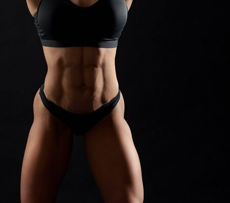 Sexy, athletic muscular torso of sportive woman. Attractive, strong female muscular body in black sportive top and panties on black background. Concept of sports and health. Banco de Imagens
