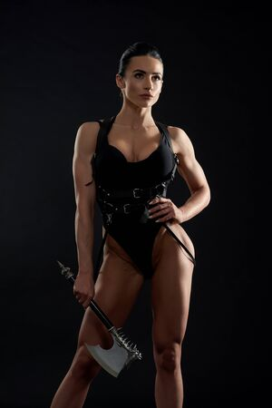 Gorgeous, sexy woman holding battle ax, wearing in black bodysuit and leather bandage. Beautiful, seductive girl with brunette hair holding hand on waist, looking at camera.