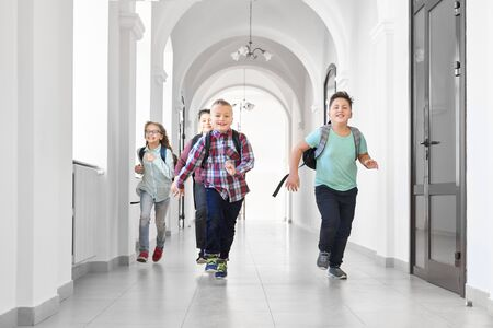 Group of happy pupils running forward on corridor of school to home, after lessons. Boys and girls having fun, playing before lessons. Break in school. Banco de Imagens
