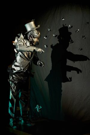 Proficient mime actor that looks like statue standing over black background wall with his shadow on it.Concept of spectacular pantomime act