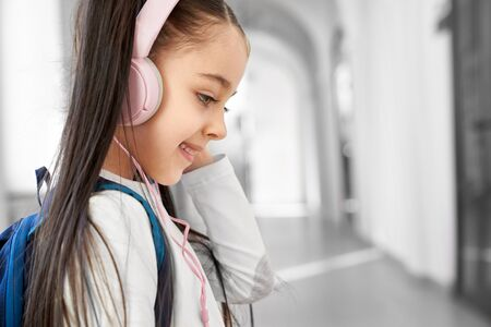 Close up of pretty brunette school girl smiling , wearing big pink headphones and looking down. Happy little girl standing on corridor of lyceum and listening music, resting after lessons.