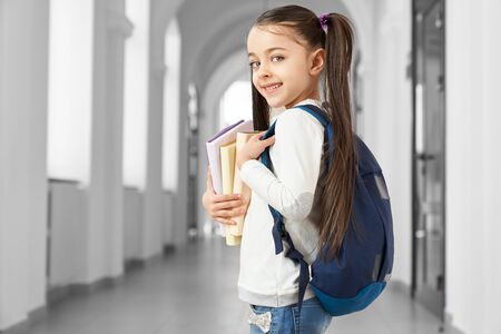 Pretty and clever school girl with funny hairstyle and backpack on shoulder going forward to corridor to her classroom. Pretty girl holding notes and book in hands resting on break among lessons.