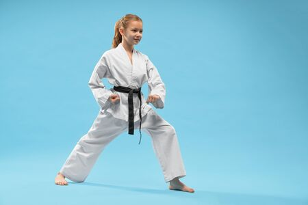 Karate girl performing defense position. Pretty child in white kimono with black belt, barefoot practicing of combat sports. Cute kid posing in studio on blue background.