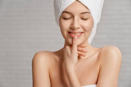 Pretty model with healthy, clean face skin in white towel on head smiling, touching lips. Beautiful, young woman with bare shoulders and closed eyes posing. Concept of skin care.