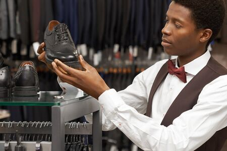Handsome man choosing stylish black shoes. Gentleman holding, looking at black footwear. Client of boutique wearing in white shirt with red bow tie.