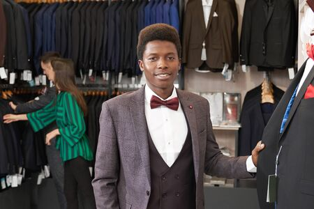 Young african man in white shirt with red bow tie, black waistcoat, grey jacket posing in fashionable boutique, standing near mannequin. Girl shop consultant helping client.