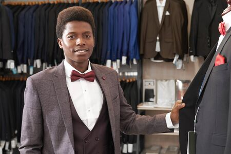 Portrait of young african man in white shirt with red bow tie, black waistcoat, grey jacket in fashionable boutique. Client of shop with clothing for men standing near mannequin with jacket, posing.
