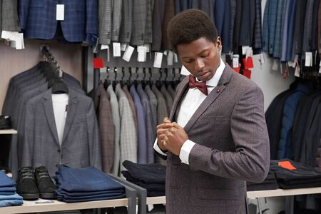 Young, african man wearing suit, fitting and looking at jacket. Client of shop posing in white shirt with red bow tie and elegant grey jacket with fashionable print. Banco de Imagens