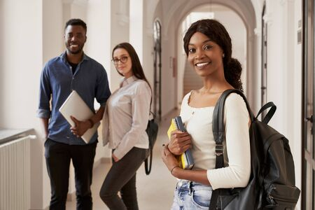 African girl smiling at camera, standing on corridor with notes and backpack. Happy couple of students on background, studying together in luxury international university.