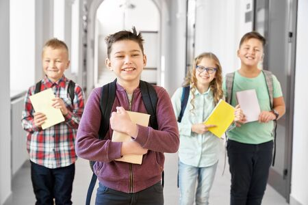 Handsome little school boy embracing book and smiling, near his friends on background. Happy pupils with notes standing on corridor and having fun together. Concept of books and studying Banco de Imagens
