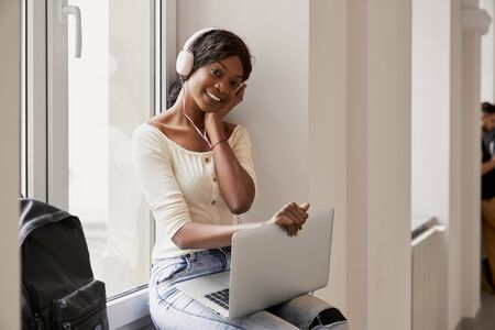 Pretty African girl listening music from big headphones and using laptop on break at university. Female student with laptop sitting on windowsill and smiling at camera.