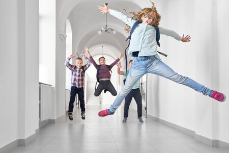 Blonde school girl jumping up and rising up by hands enjoying of studying in luxury school. Funny group of classmates on background happy jumping and gesturing by hands at side. Banco de Imagens